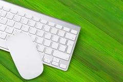 Επιχειρησιακός εργασιακός χώρος με τον υπολογιστή, το ασύρματο πληκτρολόγιο, τα κλειδιά και το ποντίκι στο παλαιό πράσινο ξύλινο  Στοκ Εικόνες