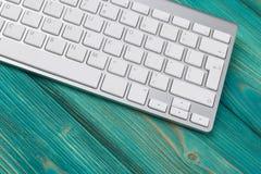 Επιχειρησιακός εργασιακός χώρος με το ασύρματο πληκτρολόγιο στο παλαιό μπλε ξύλινο επιτραπέζιο υπόβαθρο Γραφείο γραφείων με το δι Στοκ φωτογραφία με δικαίωμα ελεύθερης χρήσης