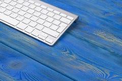 Επιχειρησιακός εργασιακός χώρος με το ασύρματο πληκτρολόγιο στο παλαιό μπλε ξύλινο επιτραπέζιο υπόβαθρο Γραφείο γραφείων με το δι Στοκ εικόνες με δικαίωμα ελεύθερης χρήσης
