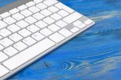 Επιχειρησιακός εργασιακός χώρος με το ασύρματο πληκτρολόγιο στο παλαιό μπλε ξύλινο επιτραπέζιο υπόβαθρο Γραφείο γραφείων με το δι Στοκ Φωτογραφίες
