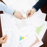 Επιχειρησιακός κόσμος και τα σύμβολά του - δύο επιχειρηματίες που εργάζονται σε μερικά οικονομικά στοιχεία σε ένα γραφείο Στοκ Φωτογραφίες