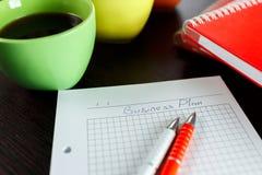 Επιχειρησιακός προγραμματισμός με τον καφέ, το σημειωματάριο, sketchbook και τη μάνδρα δύο στο σκοτεινό καφετή ξύλινο πίνακα Στοκ Εικόνα