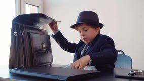 Επιχειρησιακός προϊστάμενος μικρών παιδιών στον κρύβοντας σωρό χρημάτων επιχειρησιακών πινάκων στο χαρτοφύλακα στην αρχή Νέος επι απόθεμα βίντεο