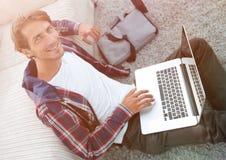 Επιχειρησιακός τύπος με τη συνεδρίαση lap-top στον τάπητα στο καθιστικό Στοκ φωτογραφίες με δικαίωμα ελεύθερης χρήσης
