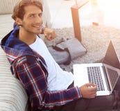 Επιχειρησιακός τύπος με τη συνεδρίαση lap-top στον τάπητα στο καθιστικό Στοκ εικόνες με δικαίωμα ελεύθερης χρήσης