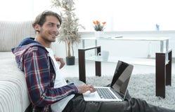 Επιχειρησιακός τύπος με τη συνεδρίαση lap-top στον τάπητα στο καθιστικό Στοκ Φωτογραφία