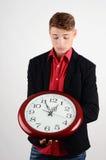 Επιχειρησιακός χρόνος. Επιχειρησιακό άτομο που κρατά και που κοιτάζει σε ένα μεγάλο ρολόι. Στοκ Εικόνες