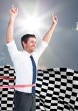 Επιχειρησιακό άτομο ενθαρρυντικό στη γραμμή τερματισμού ενάντια στον ουρανό και τον ήλιο και την ελεγμένη σημαία Στοκ Φωτογραφία