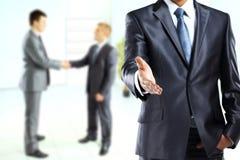 Επιχειρησιακό άτομο με ένα ανοικτό χέρι έτοιμο να σφραγίσει μια διαπραγμάτευση Στοκ Εικόνες