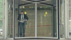 Επιχειρησιακό άτομο με τα έγγραφα και σημειωματάριο που βγαίνει από το κτίριο γραφείων που πιέζει χρονικά και που σκοντάφτει απόθεμα βίντεο