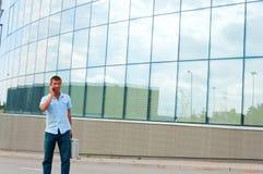 Επιχειρησιακό άτομο με την περίπτωση μετάλλων και κινητό τηλέφωνο μπροστά από το σύγχρονο επιχειρησιακό κτήριο Στοκ Εικόνες