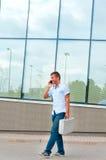 Επιχειρησιακό άτομο με την περίπτωση μετάλλων και κινητό τηλέφωνο μπροστά από το σύγχρονο επιχειρησιακό κτήριο Στοκ φωτογραφία με δικαίωμα ελεύθερης χρήσης
