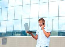 Επιχειρησιακό άτομο με το κινητό τηλέφωνο laptopand μπροστά από το σύγχρονο επιχειρησιακό κτήριο Στοκ Φωτογραφία