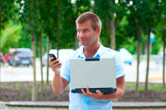 Επιχειρησιακό άτομο με το κινητό τηλέφωνο laptopand μπροστά από το σύγχρονο επιχειρησιακό κτήριο Στοκ Εικόνες