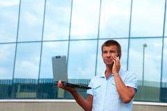 Επιχειρησιακό άτομο με το κινητό τηλέφωνο laptopand μπροστά από το σύγχρονο επιχειρησιακό κτήριο Στοκ φωτογραφία με δικαίωμα ελεύθερης χρήσης