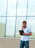 Επιχειρησιακό άτομο με το σημειωματάριο και κινητό τηλέφωνο μπροστά από το σύγχρονο επιχειρησιακό κτήριο Στοκ φωτογραφία με δικαίωμα ελεύθερης χρήσης