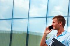 Επιχειρησιακό άτομο με το σημειωματάριο και κινητό τηλέφωνο μπροστά από το σύγχρονο επιχειρησιακό κτήριο Στοκ Εικόνες