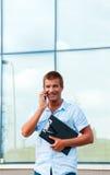 Επιχειρησιακό άτομο με το σημειωματάριο και κινητό τηλέφωνο μπροστά από το σύγχρονο επιχειρησιακό κτήριο Στοκ Φωτογραφία