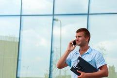 Επιχειρησιακό άτομο με το σημειωματάριο και κινητό τηλέφωνο μπροστά από το σύγχρονο επιχειρησιακό κτήριο Στοκ Φωτογραφίες
