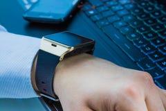 Επιχειρησιακό άτομο με το smartwatch app κοντά στο πληκτρολόγιο PC υπολογιστών και smartphone στο καθημερινό φως Στοκ Φωτογραφίες