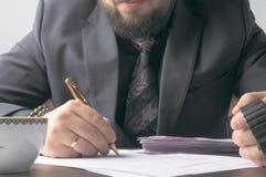 Επιχειρησιακό άτομο που γράφει μια συνθήκη ή μια σύμβαση στον πίνακα και που εργάζεται στα έγγραφα στο γραφείο, επιχειρησιακή ένν Στοκ Εικόνα