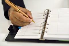 Επιχειρησιακό άτομο που γράφει στην ημερήσια διάταξη Στοκ Φωτογραφία