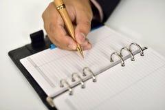 Επιχειρησιακό άτομο που γράφει στην ημερήσια διάταξη Στοκ εικόνες με δικαίωμα ελεύθερης χρήσης