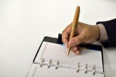 Επιχειρησιακό άτομο που γράφει στην ημερήσια διάταξη Στοκ φωτογραφία με δικαίωμα ελεύθερης χρήσης