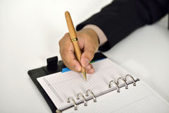 Επιχειρησιακό άτομο που γράφει στην ημερήσια διάταξη Στοκ εικόνα με δικαίωμα ελεύθερης χρήσης