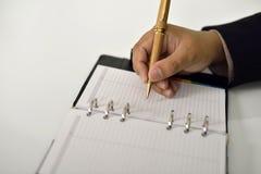 Επιχειρησιακό άτομο που γράφει στην ημερήσια διάταξη Στοκ Εικόνα