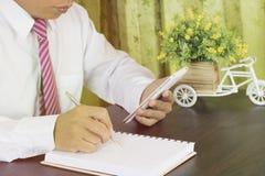 Επιχειρησιακό άτομο που γράφει στο σημειωματάριο και που φαίνεται εργασία για το τηλέφωνο στο χώρο εργασίας Στοκ φωτογραφία με δικαίωμα ελεύθερης χρήσης