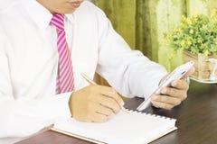 Επιχειρησιακό άτομο που γράφει στο σημειωματάριο και που φαίνεται εργασία για το τηλέφωνο στο χώρο εργασίας Στοκ Εικόνα