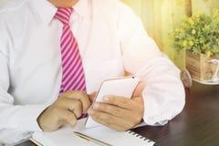 Επιχειρησιακό άτομο που γράφει στο σημειωματάριο και που φαίνεται εργασία για το τηλέφωνο στο χώρο εργασίας Στοκ Εικόνες