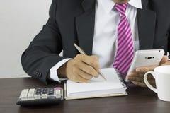 Επιχειρησιακό άτομο που γράφει στο σημειωματάριο και που φαίνεται εργασία για το τηλέφωνο Στοκ Εικόνα