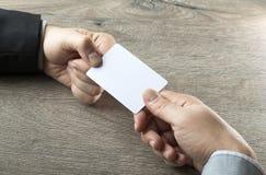 Επιχειρησιακό άτομο που δίνει τη επαγγελματική κάρτα στο συνέταιρο με το ξύλινο επιτραπέζιο υπόβαθρο Στοκ Φωτογραφία