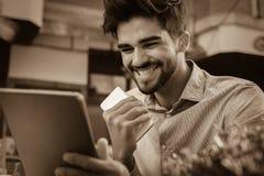 Επιχειρησιακό άτομο που εργάζεται στην ψηφιακή ταμπλέτα στον καφέ οδών στοκ εικόνα