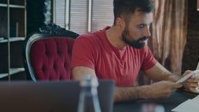 Επιχειρησιακό άτομο που εργάζεται στο lap-top και που κουβεντιάζει στο τηλέφωνο στην αρχή απόθεμα βίντεο
