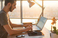 Επιχειρησιακό άτομο που εργάζεται στο lap-top στο γραφείο στην αρχή Στοκ Εικόνες