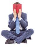 Επιχειρησιακό άτομο που κάθεται διαγώνιο με πόδια καλύπτοντας το πρόσωπό του με ένα βιβλίο Στοκ Εικόνες