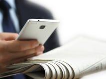 Επιχειρησιακό άτομο που κρατά μια εφημερίδα και ένα έξυπνο τηλέφωνο στο χέρι του Η άσπρη εικόνα υποβάθρου στοκ εικόνα