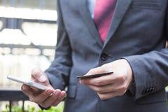Επιχειρησιακό άτομο που κρατά μια πιστωτική κάρτα και που χρησιμοποιεί το smartphone για να κάνει την κινητή πληρωμή Στοκ εικόνα με δικαίωμα ελεύθερης χρήσης