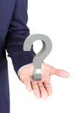 Επιχειρησιακό άτομο που κρατά μια τρισδιάστατη παλάμη χεριών ερωτηματικών διαθέσιμη Στοκ Εικόνα