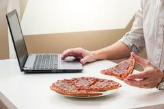 Επιχειρησιακό άτομο που κρατά μια φέτα της πίτσας, που έχει ένα γρήγορο μεσημεριανό διάλειμμα και που εργάζεται σε ένα lap-top στοκ εικόνα