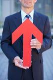 Επιχειρησιακό άτομο που κρατά το κόκκινο βέλος Στοκ εικόνα με δικαίωμα ελεύθερης χρήσης