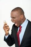 Επιχειρησιακό άτομο που κραυγάζει στο τηλέφωνο κυττάρων Στοκ Εικόνες