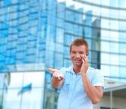 Επιχειρησιακό άτομο που μιλά στο τηλέφωνο μπροστά από το σύγχρονο επιχειρησιακό κτήριο Στοκ Εικόνα