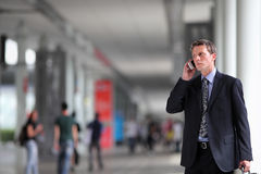 Επιχειρησιακό άτομο που μιλά στο τηλέφωνο στο πλήθος Στοκ Εικόνα