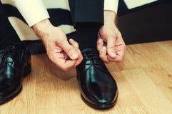 Επιχειρησιακό άτομο που ντύνει επάνω με τα κλασικά, κομψά παπούτσια Ένδυση νεόνυμφων Στοκ Εικόνα