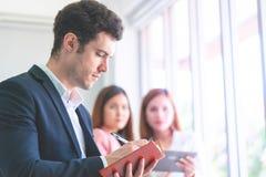 Επιχειρησιακό άτομο που παίρνει τη σημείωση μπροστά από τον εργαζόμενο γραφείων δύο θηλυκοων στοκ φωτογραφία με δικαίωμα ελεύθερης χρήσης