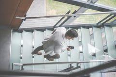 Επιχειρησιακό άτομο που περπατά στα σκαλοπάτια του επιχειρησιακού κτηρίου Επιχείρηση Στοκ εικόνες με δικαίωμα ελεύθερης χρήσης